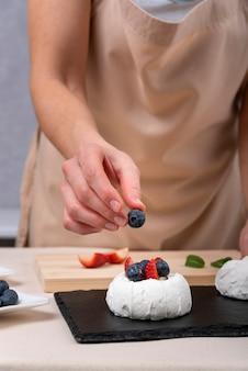 ブルーベリーとイチゴでメレンゲを飾る菓子屋
