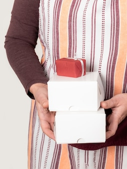 Confectioner or deliver holding two white paper boxes on the white wall.