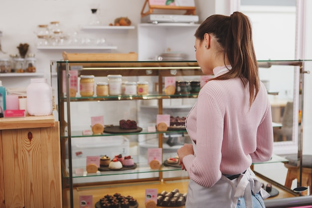Confectioner examining retail display at her cafe before opening for customers