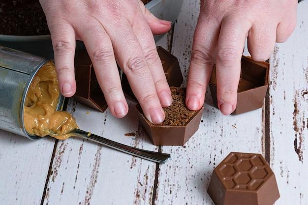 Кондитер заканчивает бразильский медовый торт рядом с жестяной коробкой с дульсе де лече.