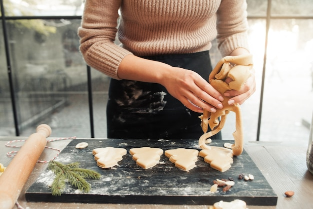 Confectioner forming christmas tree cookies on tray