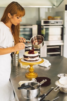 菓子屋の女の子が白いクリームとチョコレートのクッキングケーキでケーキビスケットを準備しています