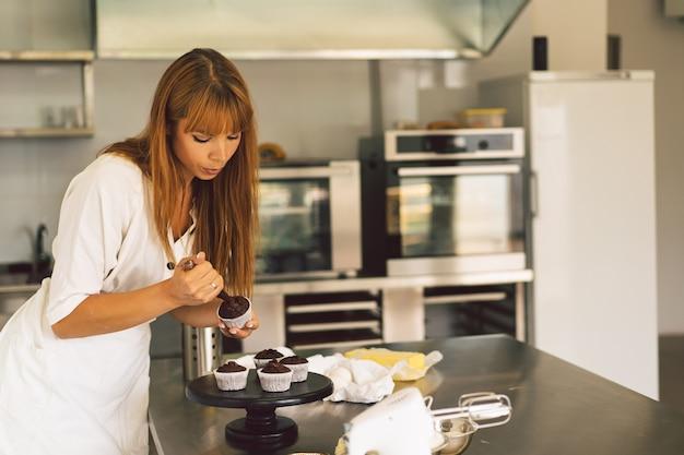 菓子屋の女の子は、小麦粉製品やデザートを調理するためのカップケーキのコンセプトの材料を準備しています