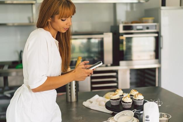 彼女のブログの女の子のためにカップケーキを撮影している菓子屋の女の子は、スマートフォンでカップケーキの写真を作ります