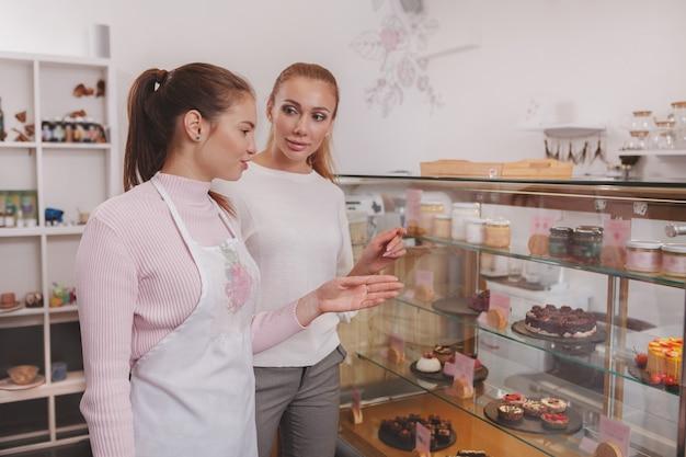 Кондитер помогает покупателю выбрать десерт с розничной витрины