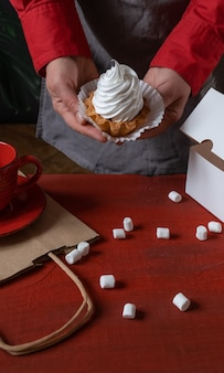 Confectioner holding white cake near white paper box and cup of coffee on red table.