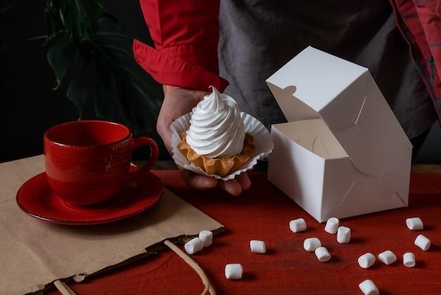 赤いテーブルの近くに白いケーキと白い紙箱を保持している菓子屋
