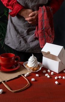 Кондитер, держащий белую бумажную коробку с белым тортом возле красного стола.