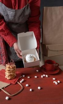 赤いテーブルの近くに白いケーキと白い紙箱を保持している菓子屋。