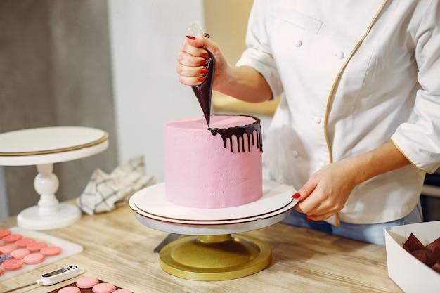 制服を着た菓子職人がケーキを飾る
