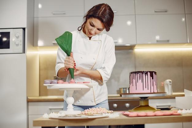 제복을 입은 제과자가 케이크를 장식합니다. 무료 사진