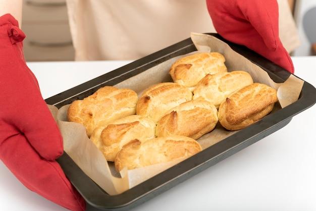 Кондитер в варежках держит противень с готовыми эклерами. вкусная домашняя выпечка.