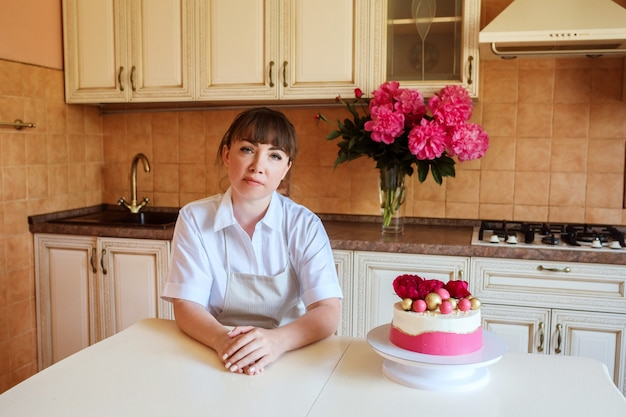 Confectioner is sitting next to her just cooked cake in the kitchen. woman freelance, business. bouquet of flowers in the background. delicious cake is decorated with flowers and chocolate balls.