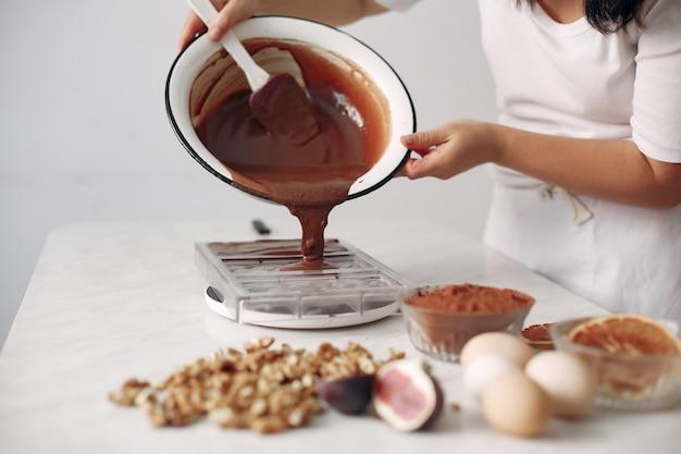 お菓子屋さんが具材を混ぜます。女性がデザートを準備しています。女性がケーキを焼きます。