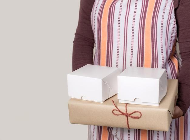 Кондитер или доставьте, держа две белые и одну бумажную коробки на белой поверхности.