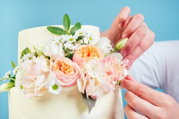 菓子職人のパティシエの女性の手は、青い背景のスタジオで新鮮な花で食欲をそそるクリーミーな白い2層のウエディングケーキを飾る