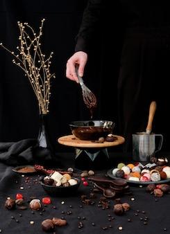 Кондитер готовит горячий шоколад на черном фоне