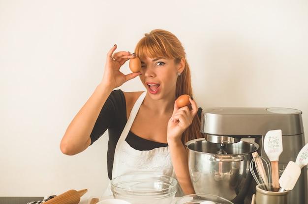 Рыжая девушка кондитер держит в руке яйца