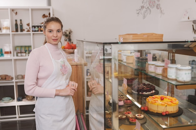 Confectioner smiling to the camera working at her raw vegan confectionery