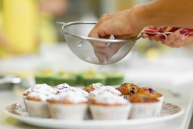 製菓業者は、焼きたてのマフィンに粉砂糖を振りかける。甘いペストリー、レシピ、料理