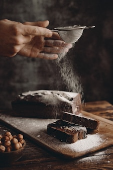 Confectioner sprinkles powdered chocolate brownie with powdered sugar