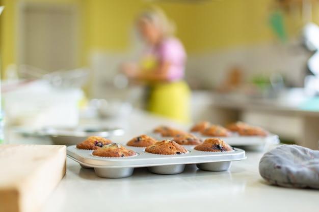 菓子職人はオーブンからテーブルのグラタン皿に焼きたてのマフィンを取り出した