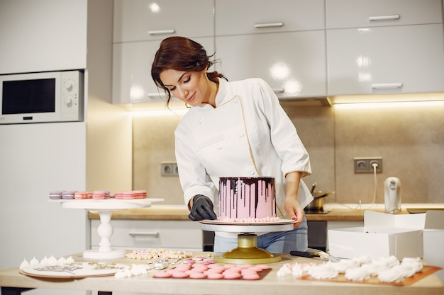 Confectioner in a uniform decorates the cake
