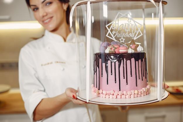 Il pasticcere in uniforme decora la torta