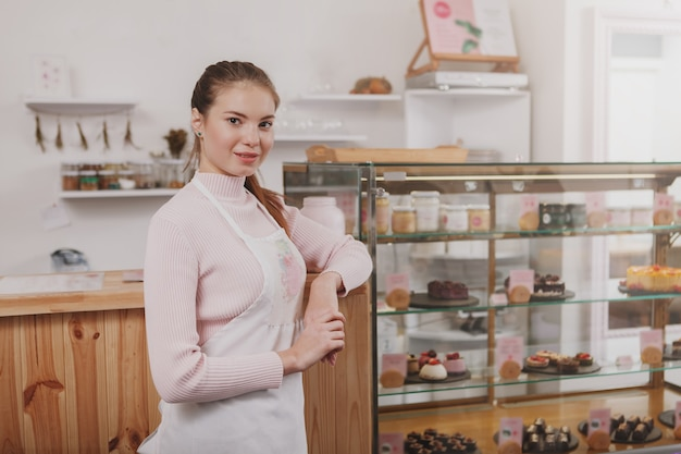 Confectioner welcoming you at her cafe, delicious desserts for sale on retail display