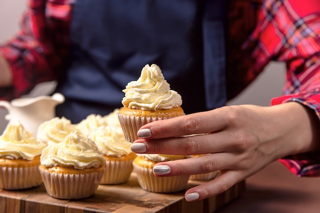 A confectioner woman in a blue apron is holding a tiramisu cupcake