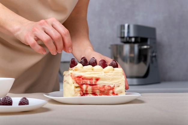 Женщина-кондитер украшает торт малиной. ванильный кремовый торт с ягодной начинкой.