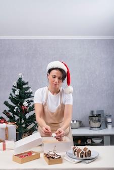 앞치마를 입은 제과 여자는 과자와 진저 브레드로 크리스마스 선물 상자를 채웁니다. 휴가. 수직 프레임.