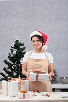 エプロンの菓子職人の女性は、お菓子のギフトボックスを保持しています。休日。垂直フレーム