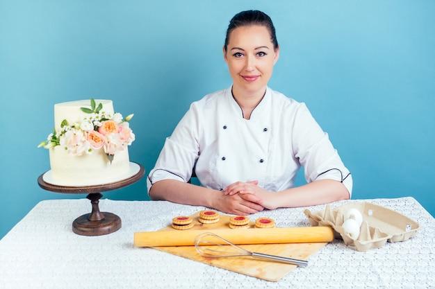 Кондитер женщина в кондитерской куртке улыбается кремово-белый двухуровневый свадебный (день рождения) торт со свежими цветами на столе в студии на синем фоне. концепция праздника и подготовка мероприятия