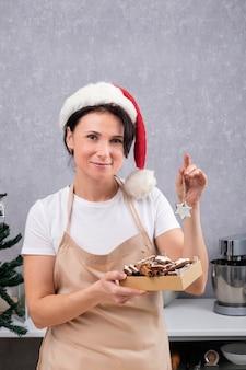 サンタの帽子とキッチンローブの菓子職人の女性は、おいしいクッキーとウィンクの箱を持っています。垂直フレーム。