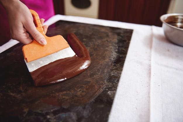 大理石の表面に溶けたチョコレートの塊を焼き戻す作業をしている菓子職人。世界チョコレートデーのためのチョコレートボンボンの製造