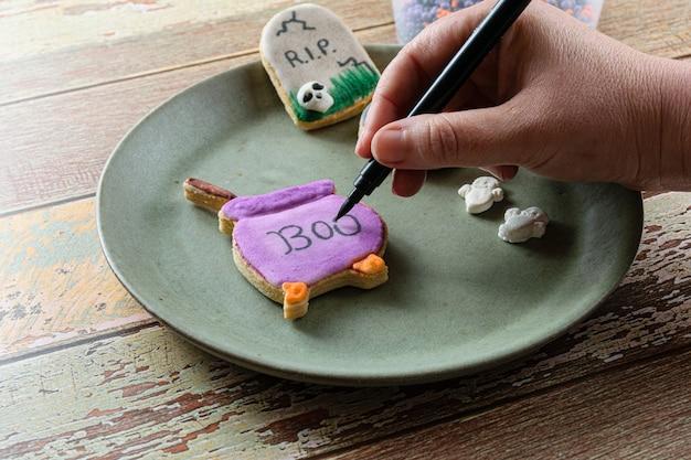 보라색 가마솥 모양의 버터 바른 비스킷에 글을 쓰는 제과자(전면 보기).