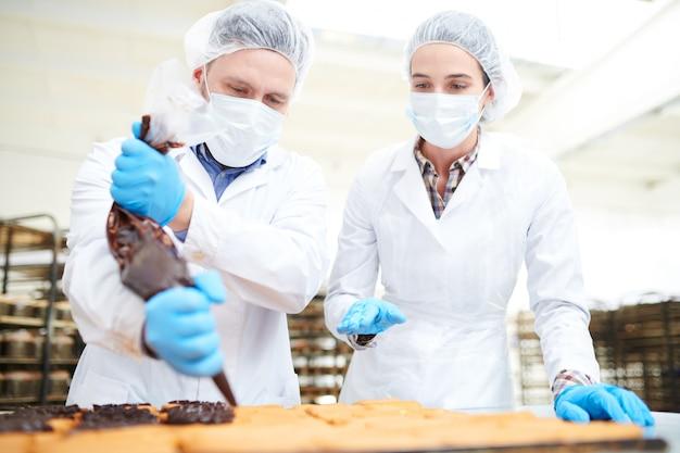 Кондитеры наливают шоколадный крем из кондитерского мешка