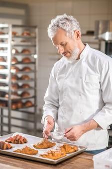 Выпечка кондитерских изделий. седовласый внимательный мужчина в белой форме, украшающий готовые круассаны на подносе в пекарне