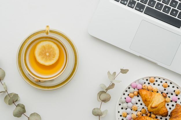 Confectionery and croissant on plate with lemon tea near the open laptop on white background