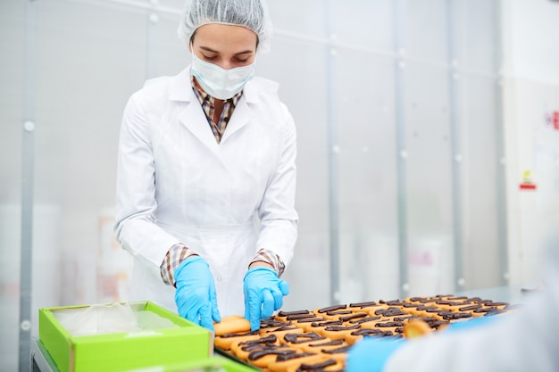 Confectionery factory worker packing ready pastry