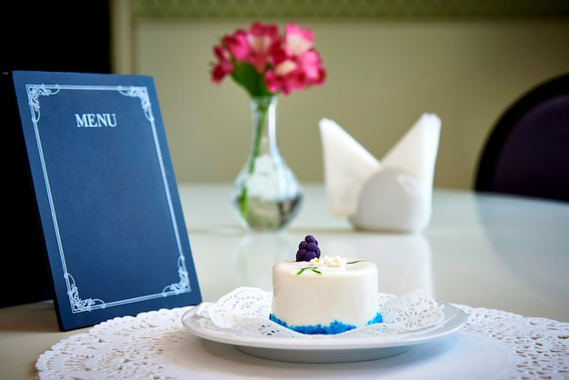 A confectionery product on a white plate with lace stands on a table with an empty layout of the menu.