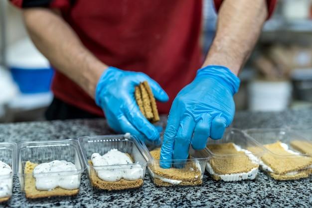맛있는 디저트를 장식하는 과자 봉지가있는 confectors 손