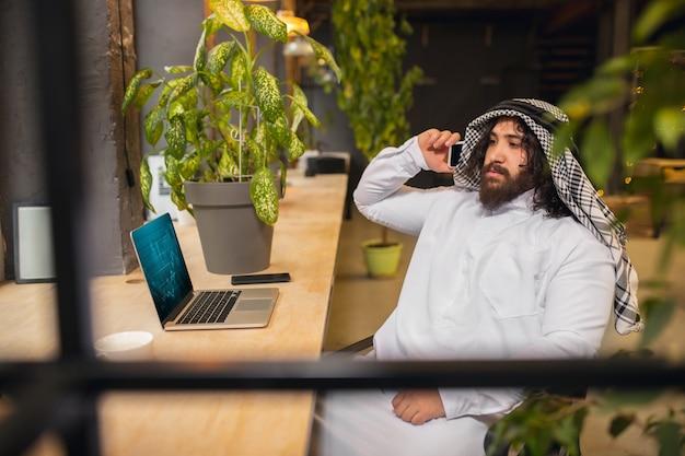 회의. 사무실에서 일하는 아라비아 사업가, 장치, 가제트를 사용하는 비즈니스 센터. 현대 사우디 라이프 스타일. 전통 의상과 스카프를 입은 남자는 자신감 있고 바쁘고 잘 생겼습니다. 민족, 금융.