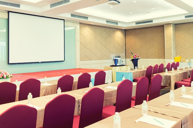 Conference meeting room , row of  chairs with stage and empty screen for business meeting, conferenc