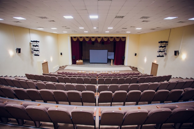 Conference meeting room with ceiling led lights, row brown chairs, with stage and empty screen for business meeting, conference