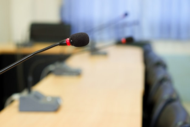 Conference microphones in a meeting room is blurred in the  background.