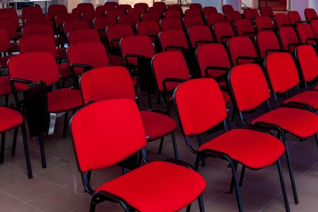 Конференц-зал с красной сценой и красными стульями для мероприятий, конференций и семинаров.