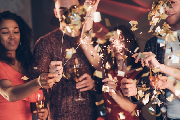 Confetti in the air. multiracial friends celebrate new year and holding bengal lights and glasses with drink