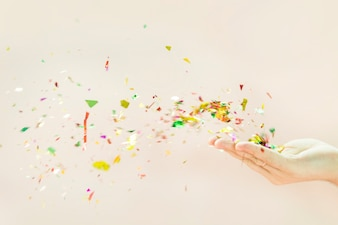 Confetti blowing from hands against beige background